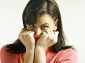 Woman covering face with turtleneck looking at the camera