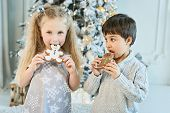 Boy And Girl Sit On Floor Under Christmas Tree. Children Eat Ginger Man. Waiting For Christmas. Cele poster