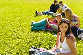 Students studying sitting on grass in park happy teens campus