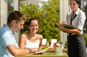 Couple at cafe ordering from menu waitress man point menu