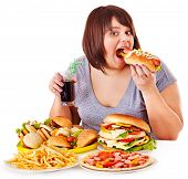 Overweight woman eating fast food.