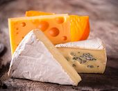 Various types of cheese on wooden background