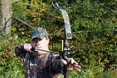 stock photo of camoflage  - bow hunter in camouflage draws back a compound