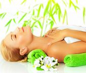 Closeup portrait of beautiful young lady in spa salon, attractive woman sleeping on massage table, side view of girl lying down with closed eyes enjoy dayspa, bamboo background and orchid flower poster