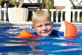 Young boy wearing inflatable floating wings learning to swim in an outdoor pool