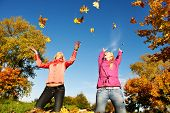two young woman with throwing up autumn maple leaves in park at fall outdoors