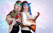 foto of mummer  - Two russian beauties with folk attributes on the shining light background - JPG