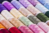 Multi-coloured cotton reels textured background