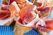 typical spanish pincho de jamon, spanish ham served on bread, on a blue background