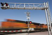 stock photo of railroad-sign  - cargo Train speeding by railroad crossing in the country - JPG