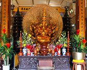 stock photo of monk fruit  - The gold statue of the Buddha is in the temple against flowers and fruit - JPG