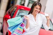 Happy woman shoppping with credit card to win a car