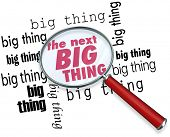 A magnifying glass on the words The Next Big Thing to illustrate finding the latest or newest trend,