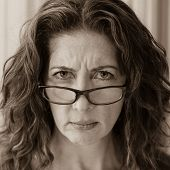 picture of frown  - Middle aged female teacher frowning over her glasses - JPG