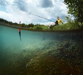 pic of catching fish  - Young smiling man fishing on a green pond - JPG