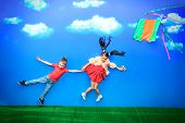Two happy children flying together on a kite in a bright summer day.