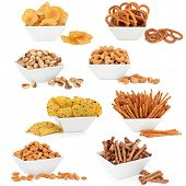 Crisps, tortillas, nuts and pretzel snack food selection in porcelain dishes over white background.