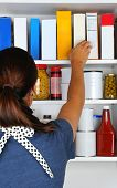 Closeup of a woman reaching into her pantry for a box of cereal. The well stocked cabinet is full of canned food, boxes, and bottles of typical grocery items. Items have blank labels.
