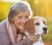 pic of dog-walker  - Senior woman hugs her beagle dog in countryside - JPG