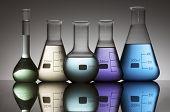 still life of five laboratory flasks photographed backlit