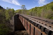 stock photo of trestle bridge  - A railroad bridge crossing a creek below - JPG