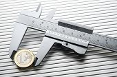 metal caliper measuring a one euro coin  on a metal surface