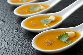 gazpacho  in a group of small spoons  on a table slate