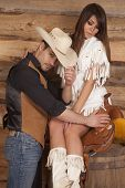 image of western saddle  - A cowboy is tipping his hat while a woman is sitting on a saddle - JPG