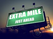Extra Mile Just Ahead on Green Billboard.