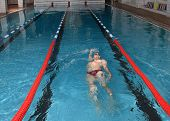 Man Floats On His Back In The Indoor Public Swimming Pool.