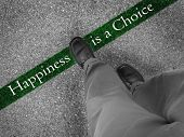 Man walking across a green line with words happiness is a choice