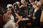 Beautiful women in evening dresses playing poker