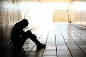 image of depressed teen  - Backlight of a teenager depressed sitting inside a dirty tunnel - JPG