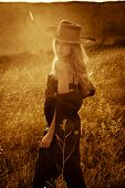young woman in cowboy style clothes outdoor at sunset,