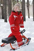 Winter In The Woods Stands A Boy On Snow Scooter And Smiling.