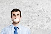 Young handsome businessman with adhesive tape on mouth