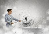 Image of businesswoman crushing with hammer pile of keyboards