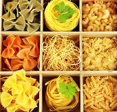 Nine types of pasta in wooden box sections close-up isolated on white