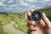 Man Using A Compass While Sightseeing Abroad