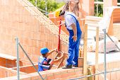 Two builder or worker with helmets controlling walls in scaffold with a bubble level on building or