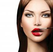 Beauty fashion model girl applying red lipgloss. Lipstick. Professional Make-up. Makeup. Lipgloss. Lipstick Brush. Sexy and Glossy Lips