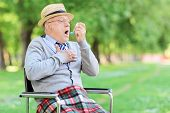 Senior man having an asthma attack in a park