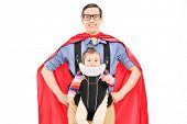 Male superhero carrying his baby daughter isolated on white background