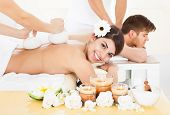foto of reflexology  - Portrait of happy woman receiving massage with herbal compress stamps on back at spa - JPG