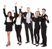 Successful Welldressed Businesspeople With Arms Raised