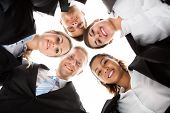foto of huddle  - Low angle portrait of business people forming huddle against white background - JPG