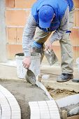 pic of masonic  - Mason worker making sidewalk pavement with stone blocks - JPG