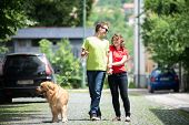 Happy young couple with a dog walking down the street