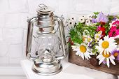 Beautiful flowers in crate with kerosene lamp on wooden stand on light background