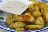 Fried potato wedges with garlic dip on the side